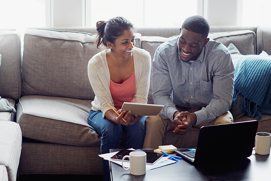African American couple sitting on a couch looking at their finances on paper while their laptop is open
